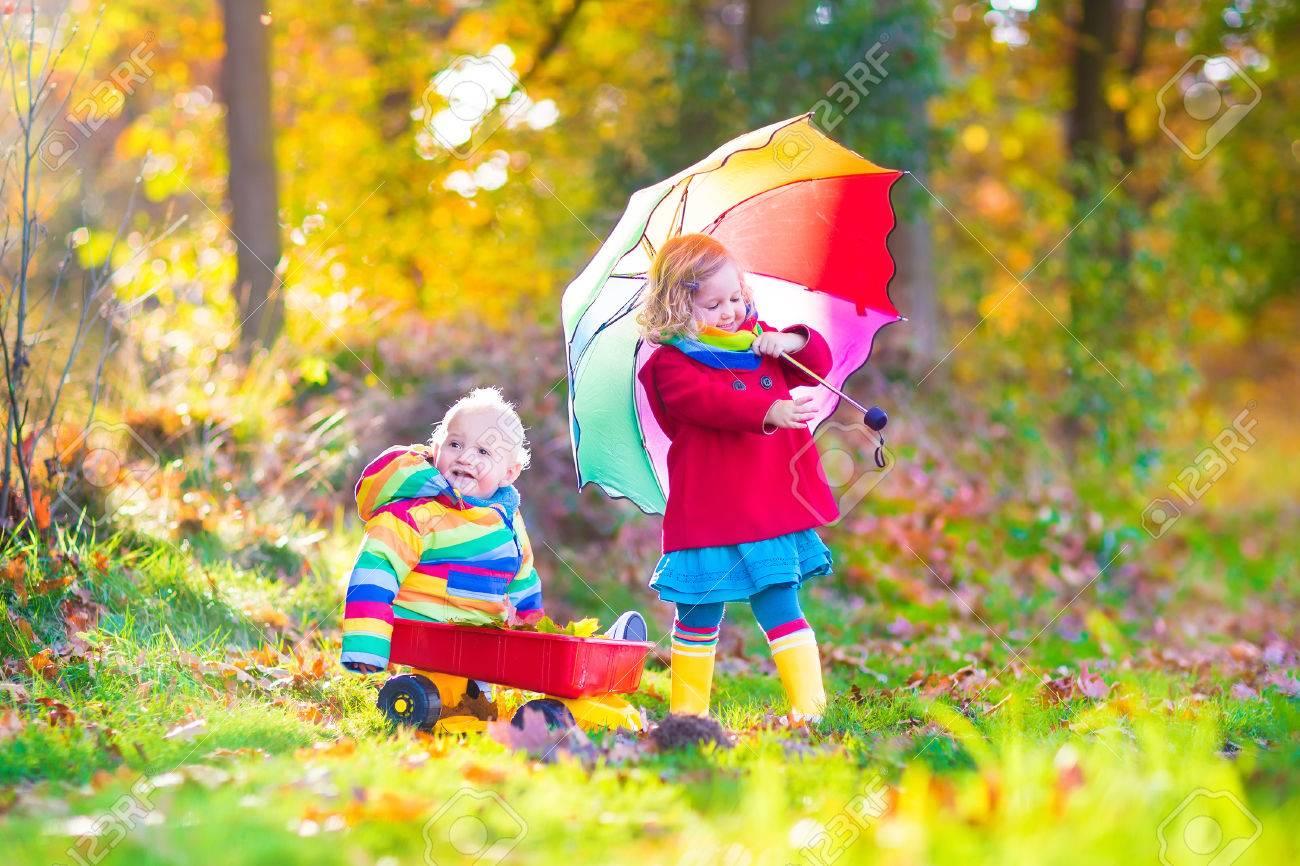 ... adorable fille de bébé et un bébé garçon drôle, frère et s ur, jouant  dans un parc d automne ensoleillée avec une brouette et un parapluie coloré 1d792e43a1a