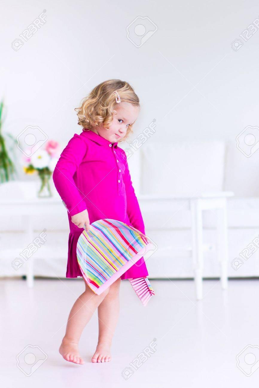 Niña Rizado Divertido Con Un Vestido Rosa Ayudar En Casa Limpiando ...