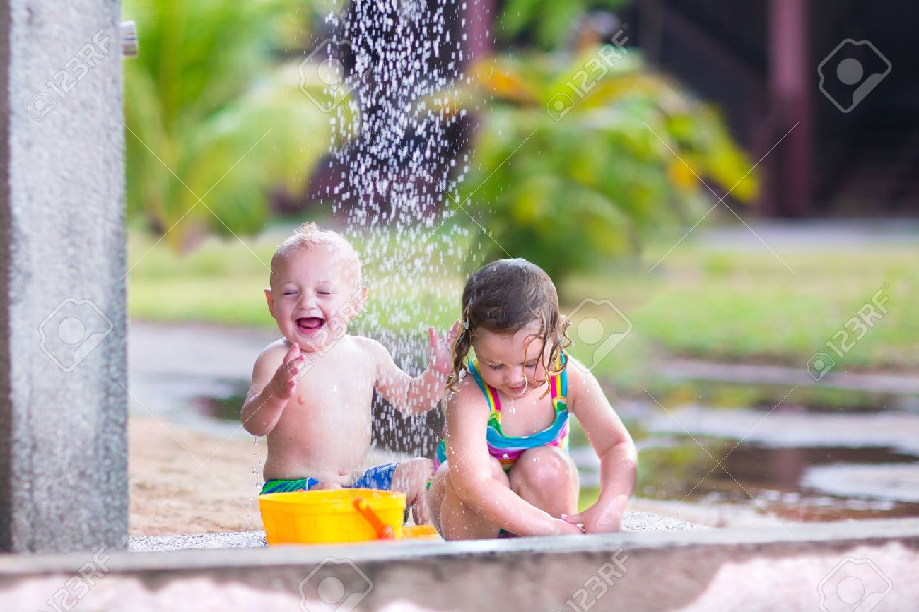 Children in shower Two happy children, adorable baby boy and a little toddler girl in swimming  suits playing