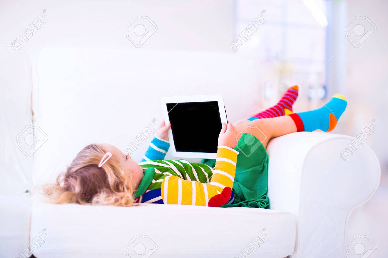 Funny Little Toddler Girl With Tablet Pc Relaxing On A White.. Stock ...