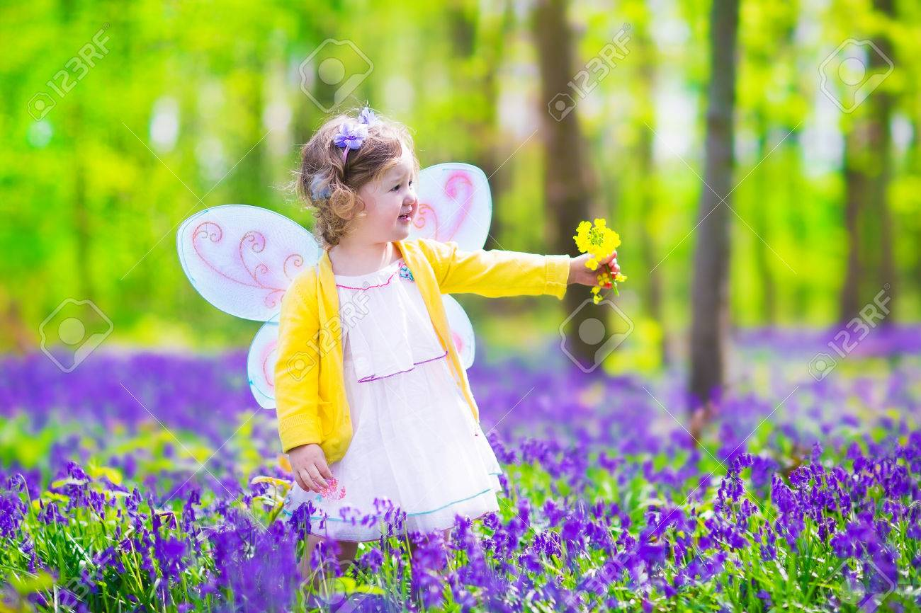 4261cfec8 Adorable toddler girl with curly hair wearing a fairy costume with purple  wings and yellow dress is playing in a beautiful spring forest with fresh  blooming ...