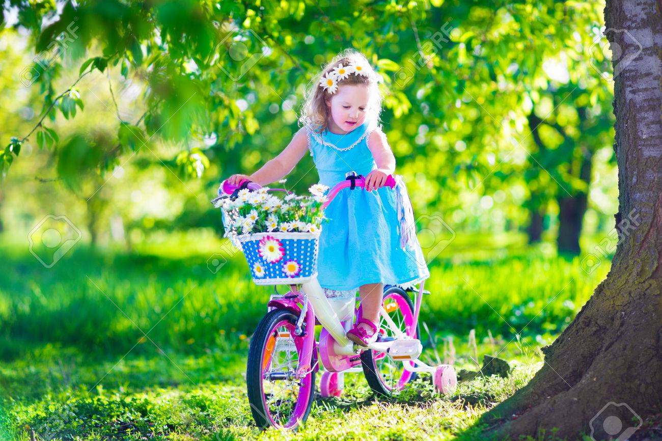 5e4128389d077 Happy Child Vélo. Cute Kid Bike Extérieur. Petite Fille Dans Une Robe Bleue  Sur Un Vélo Rose Avec Des Fleurs De Marguerite Dans Un Panier.