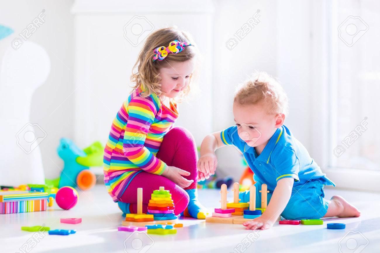 木のおもちゃで遊ぶ子供たち。2 人の子供、かわいい幼児の女の子