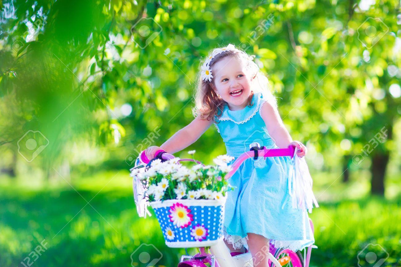happy child riding a bike. cute kid biking outdoors. little girl