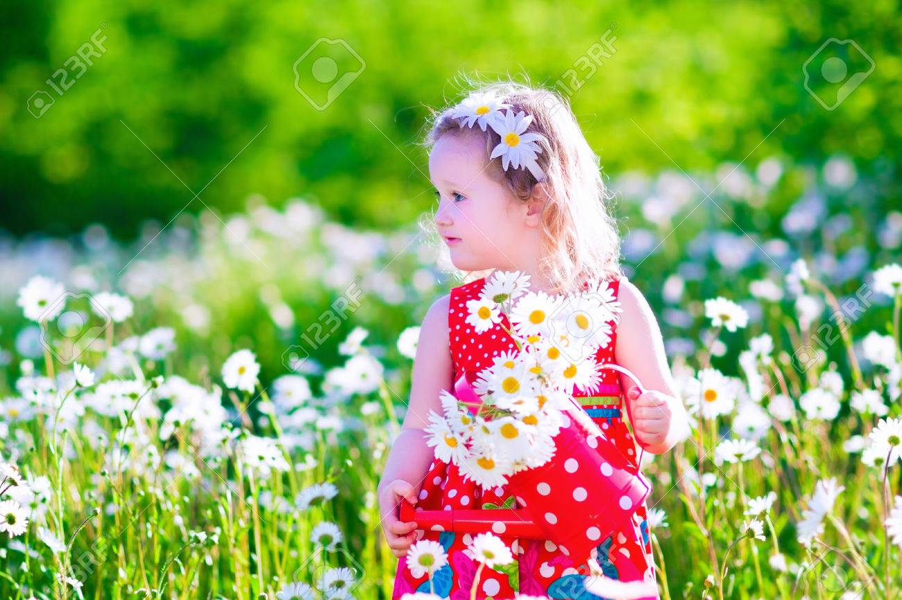 kid gardening little with water can in a daisy flower field