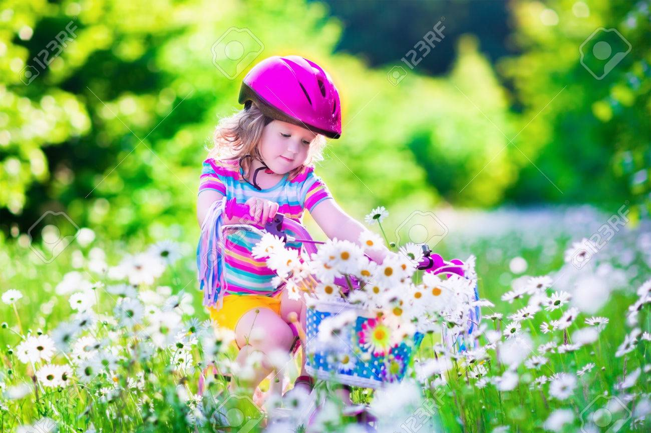 happy child riding a bike. cute kid in safety helmet biking outdoors
