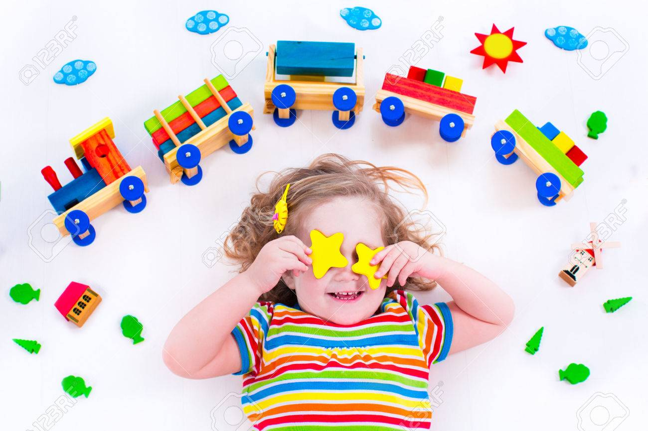 Child playing with wooden train. Toy railroad for kids. Toddler kid at day care. Educational toys for preschool and kindergarten child. Little girl at daycare. - 40446178