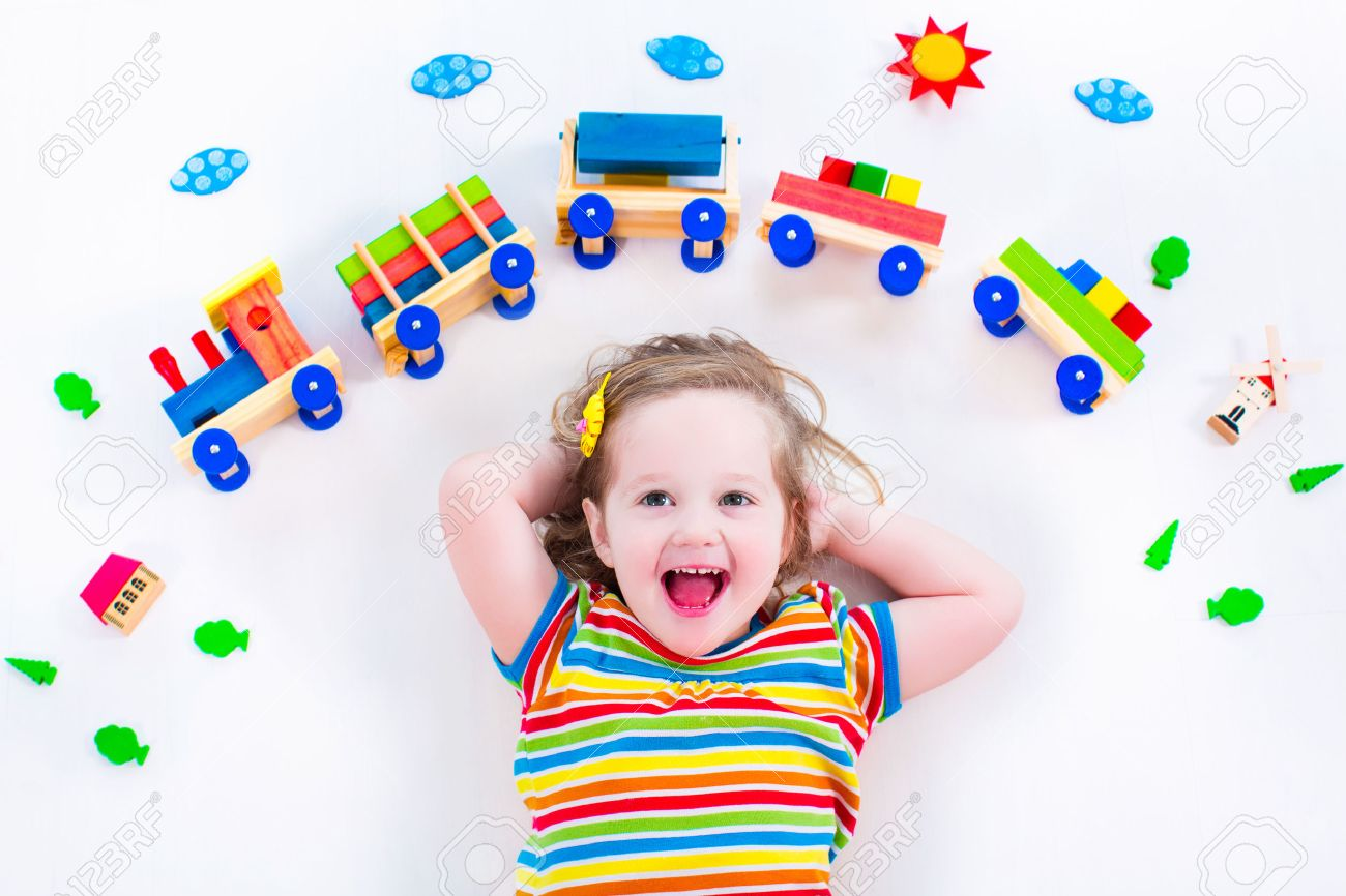 Child playing with wooden train. Toy railroad for kids. Toddler kid at day care. Educational toys for preschool and kindergarten child. Little girl at daycare. - 40446185