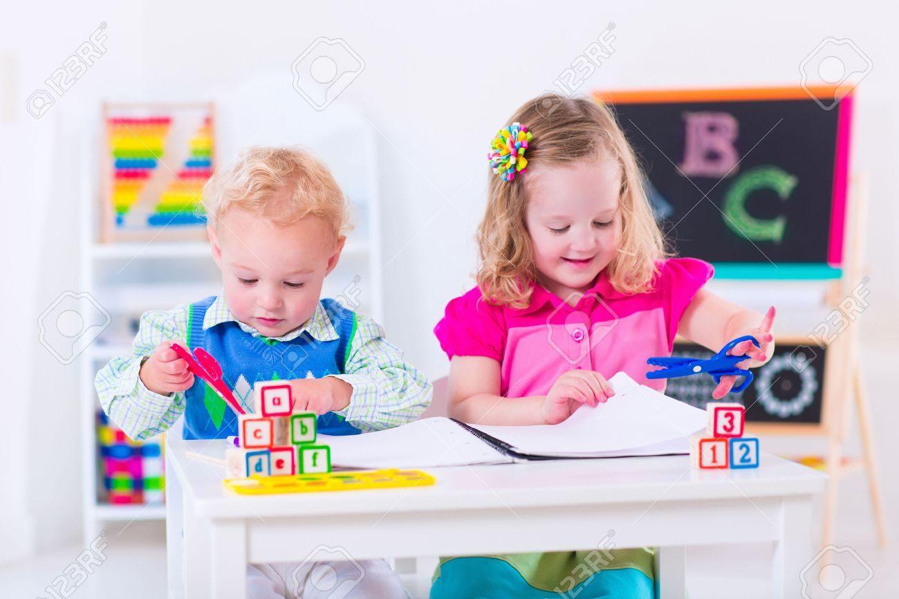 kids at preschool two children drawing and painting at kindergarten boy and girl happy - Children Painting Images