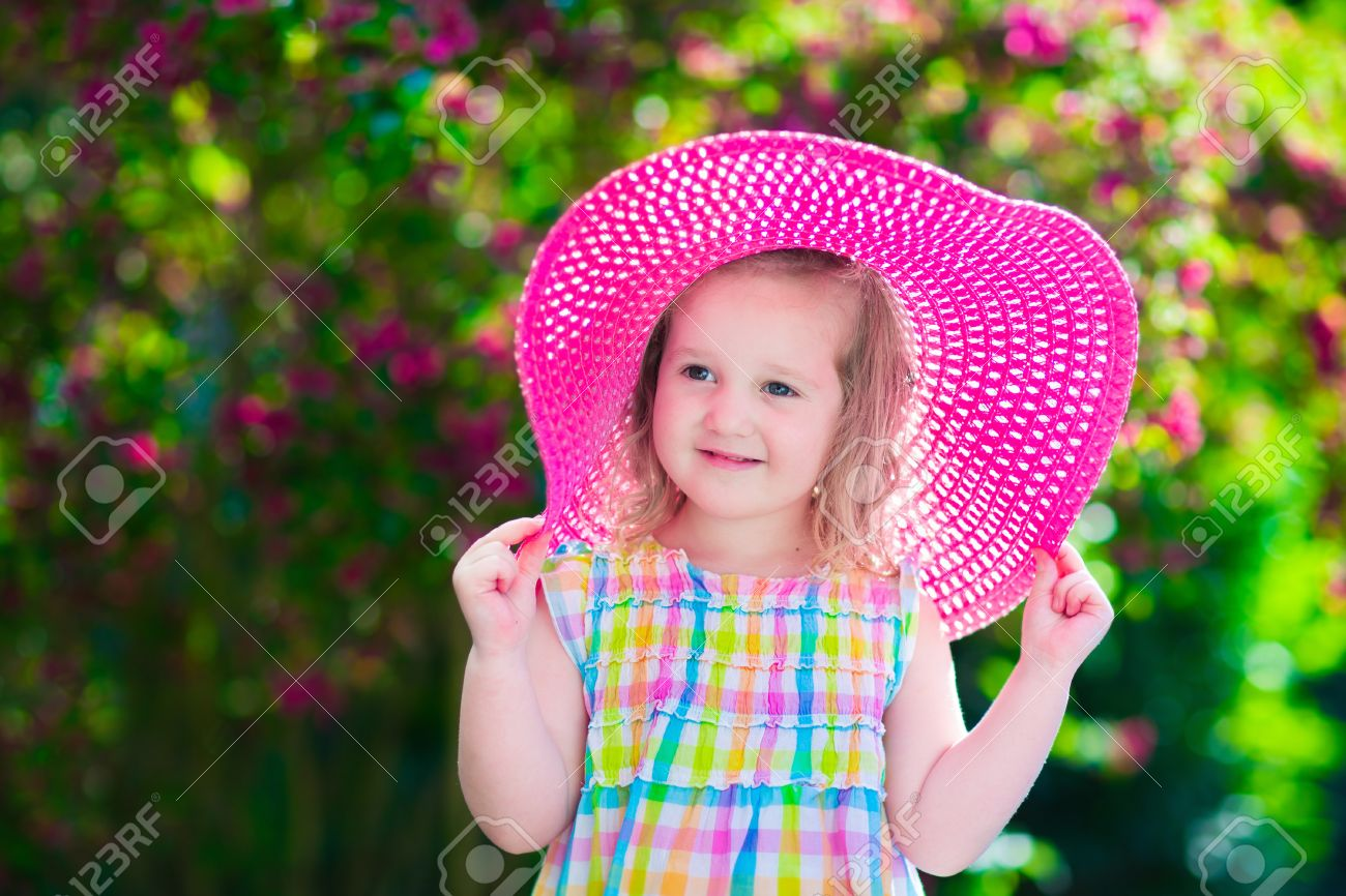 little cute girl with flowers. child wearing a pink hat playing