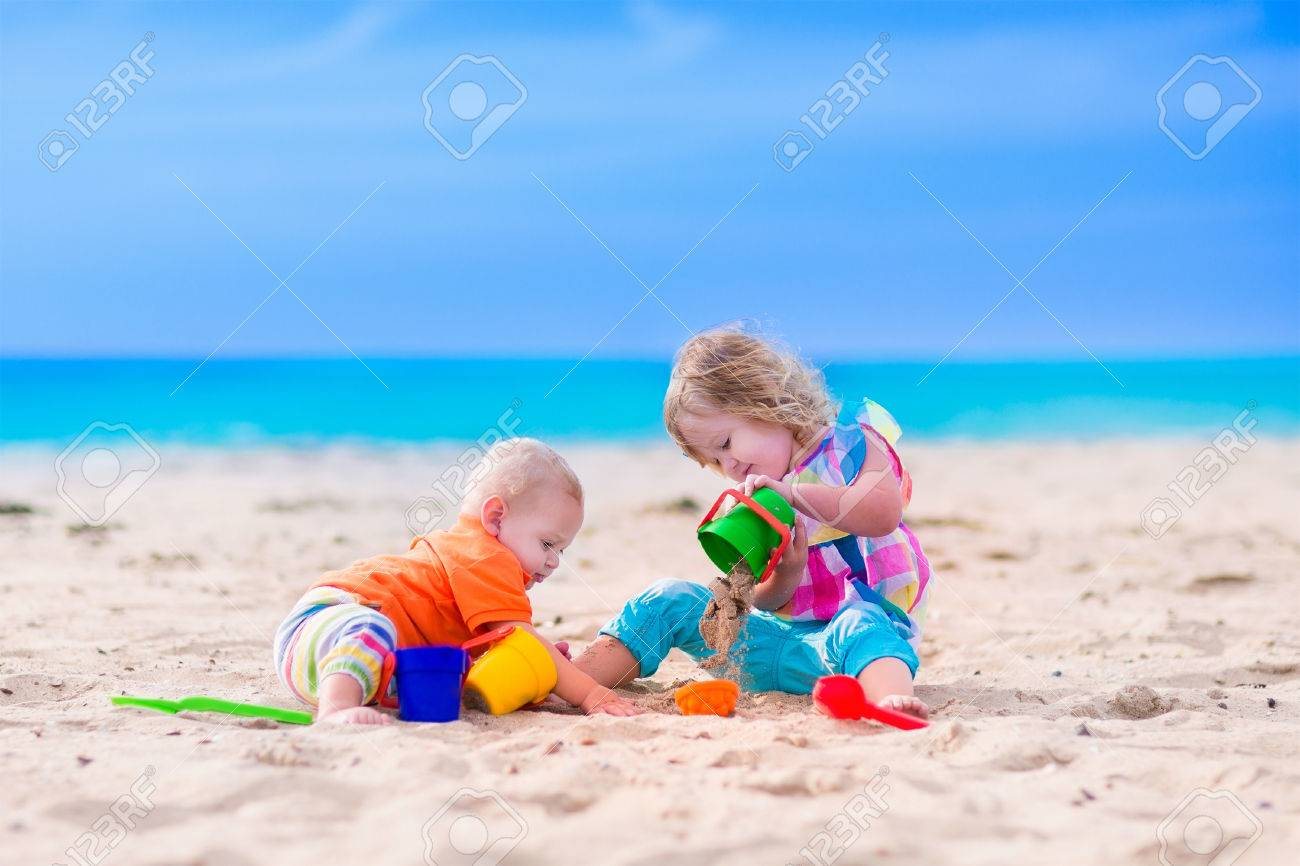 kids play water Kids play on a beach. Children building sand castle on tropical island. Summer water
