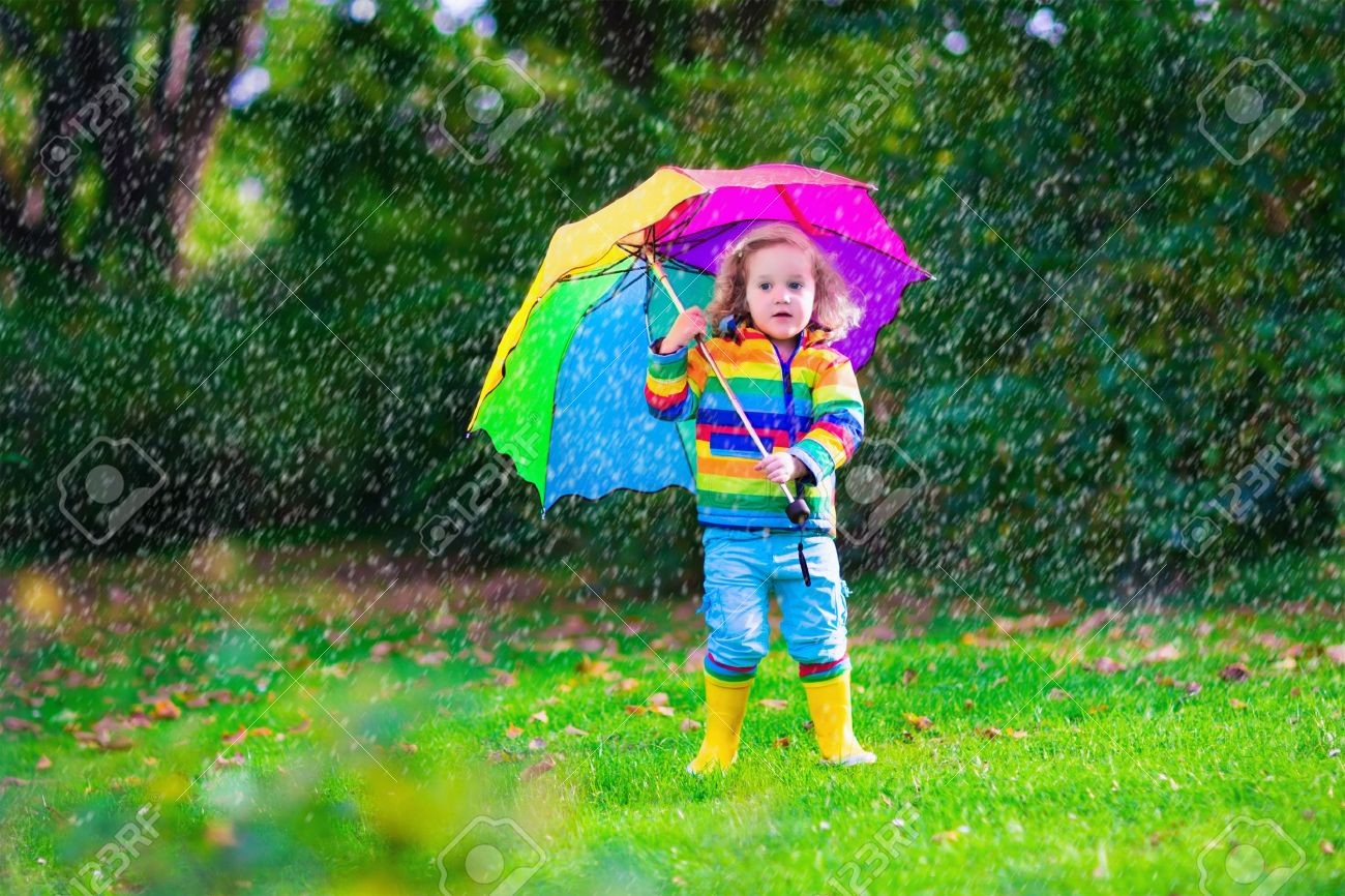 child with colorful umbrella playing in the rain kids play