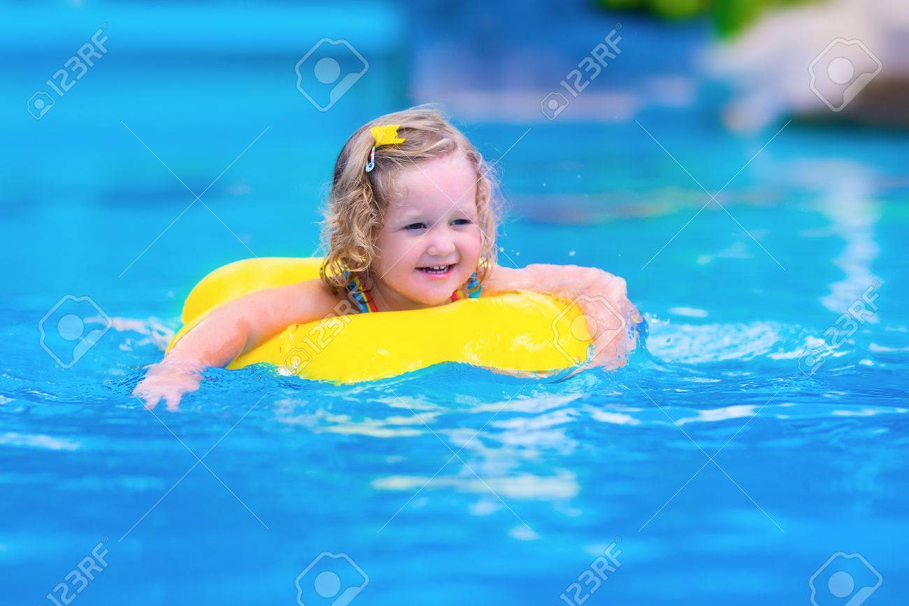 Kids in swimming pool. Children swim outdoors. Toddler child..