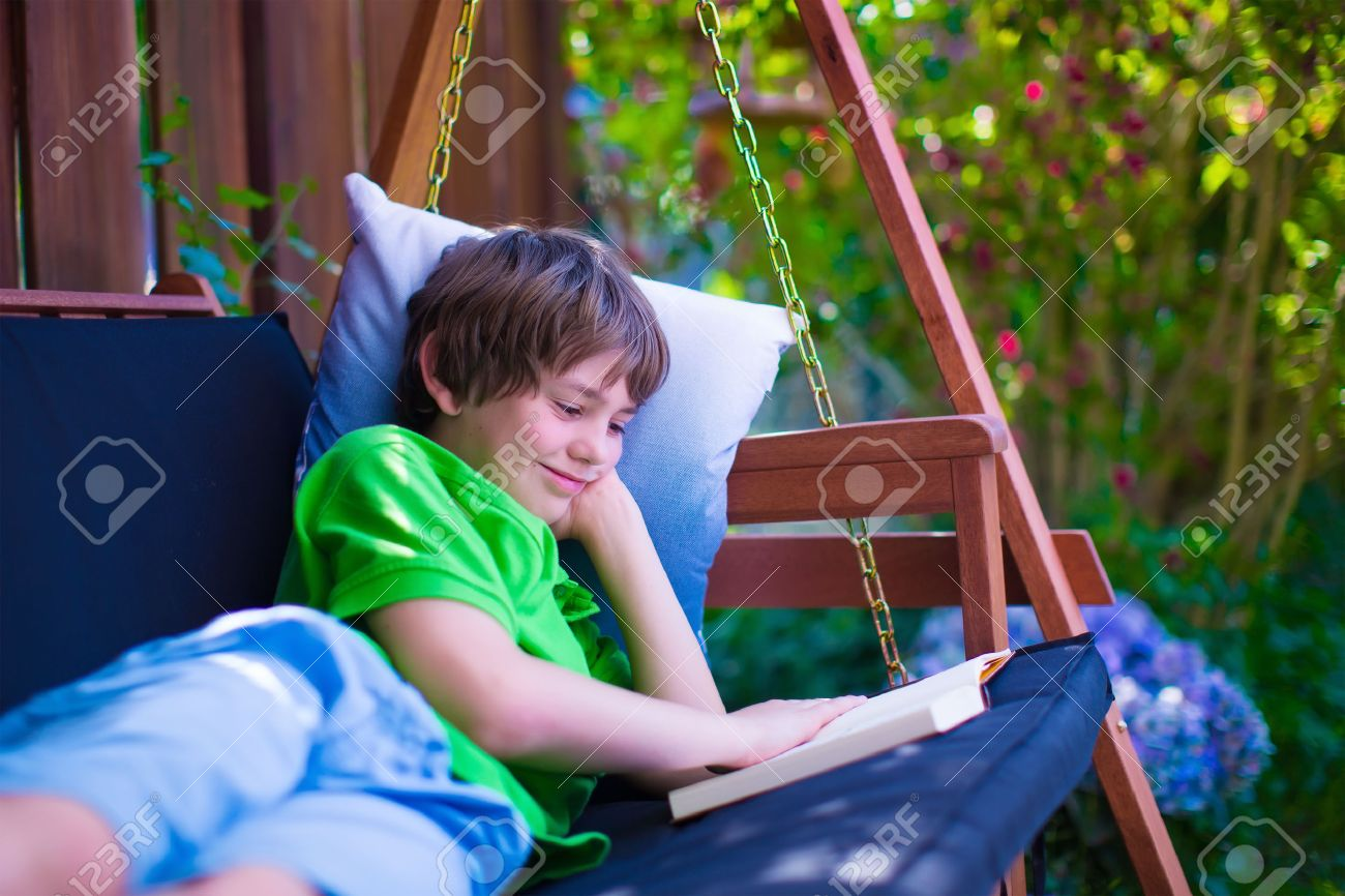 Happy School Boy Reading A Book In The Backyard. Child Relaxing In A Garden  Swing