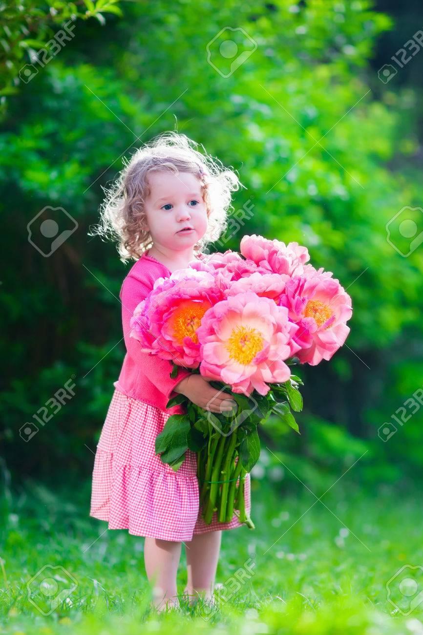 Niña Linda Con Flores De Peonía. Niño Que Llevaba Un Vestido De ...
