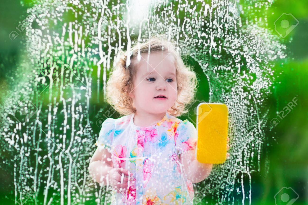 Kids Clean The House. Children Help At Home. Toddler Kid Cleaning Windows  And Doors Standing On A Ladder. Child Helping With Housework Holding Sponge  And ...