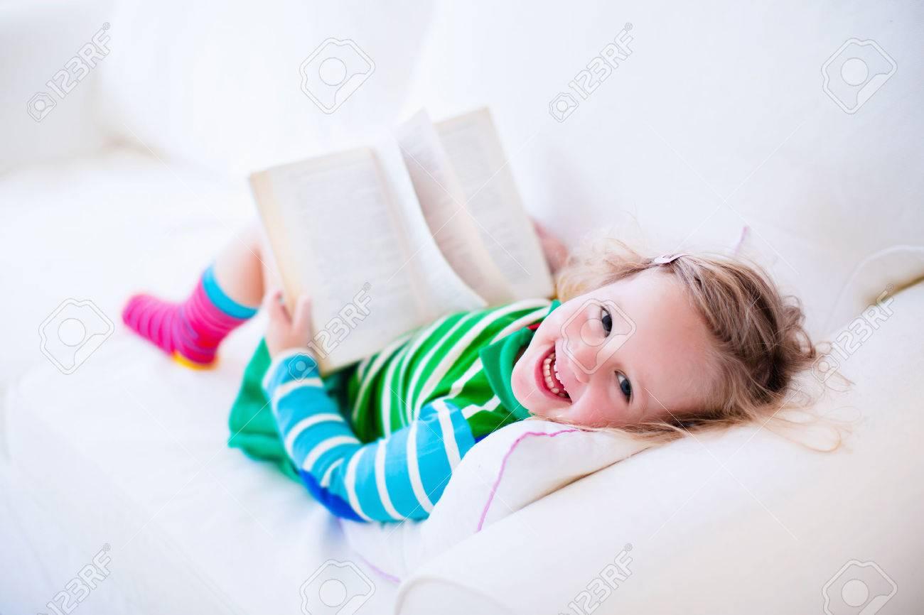 Immagini Stock Bambina Che Legge Un Libro Di Relax Su Un Divano Bianco Bambini Leggono Libri A Casa O In Eta Prescolare I Bambini L Apprendimento E Fare I Compiti Dopo La