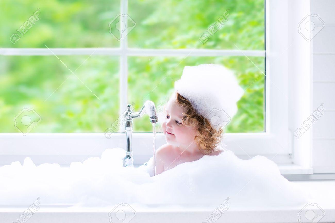 Child Taking Bath. Little Baby In A Bath Tub Washing Hair With ...