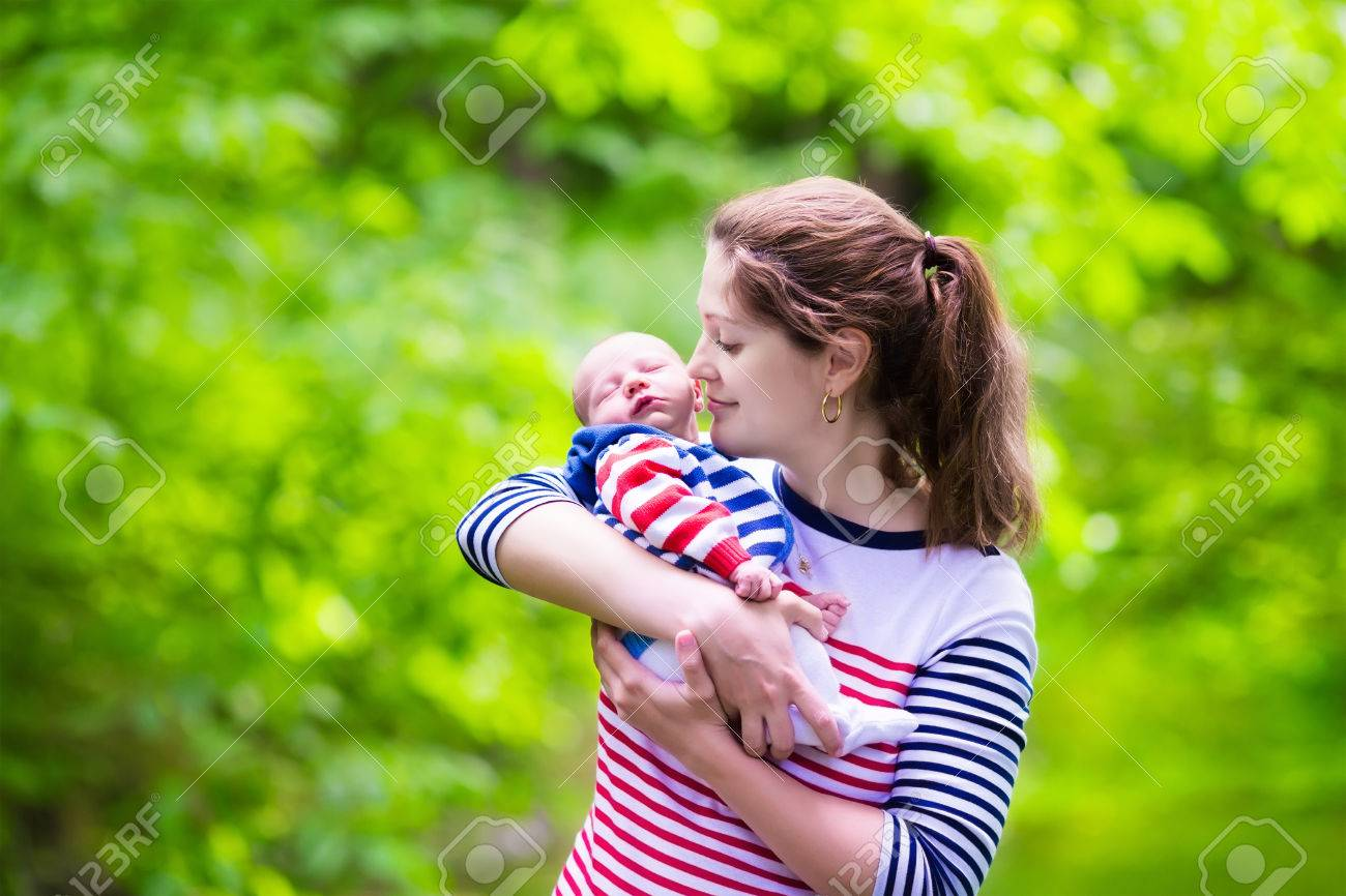 Mother holding newborn baby in a park mom playing with her new born son in the garden family with kids play outdoors young woman hugging little boy
