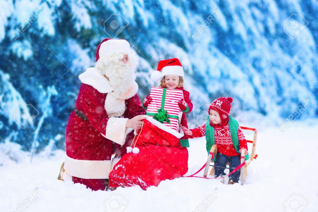 Santa Claus Und Kinder Geschenke Im Schneebedeckten Wald öffnen ...