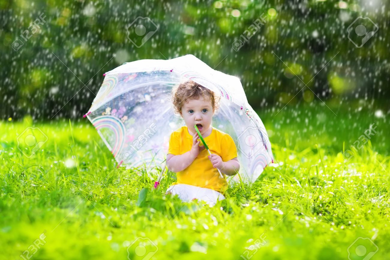 little with colorful umbrella playing in the rain kids