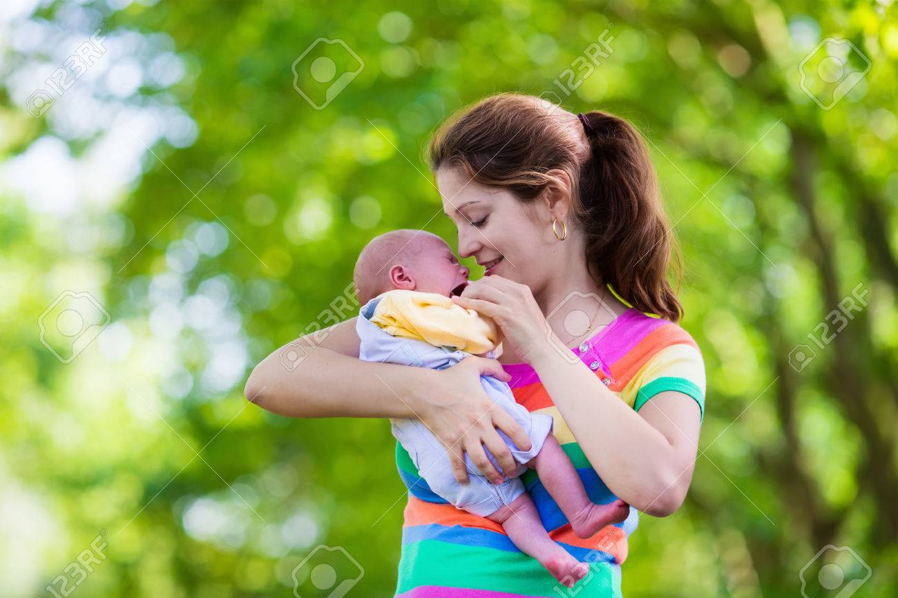 Mother holding newborn baby in a park mom playing with her new born son in