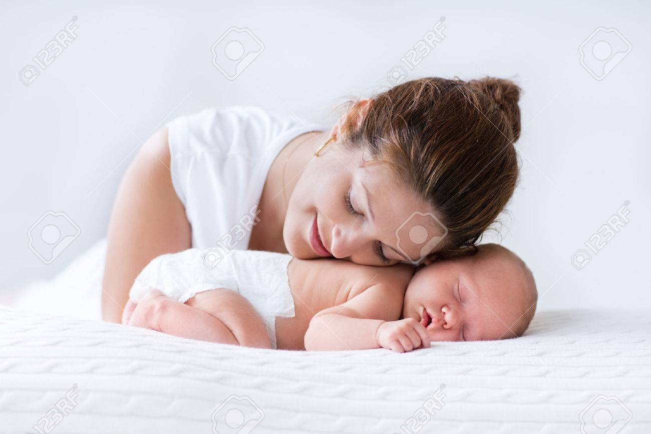 Young mother hugging her newborn child. Mom nursing baby. Woman and new born boy relax in a white bedroom. Family at home. Love, trust and tenderness concept. Bedding and textile for nursery. Stock Photo - 43360718