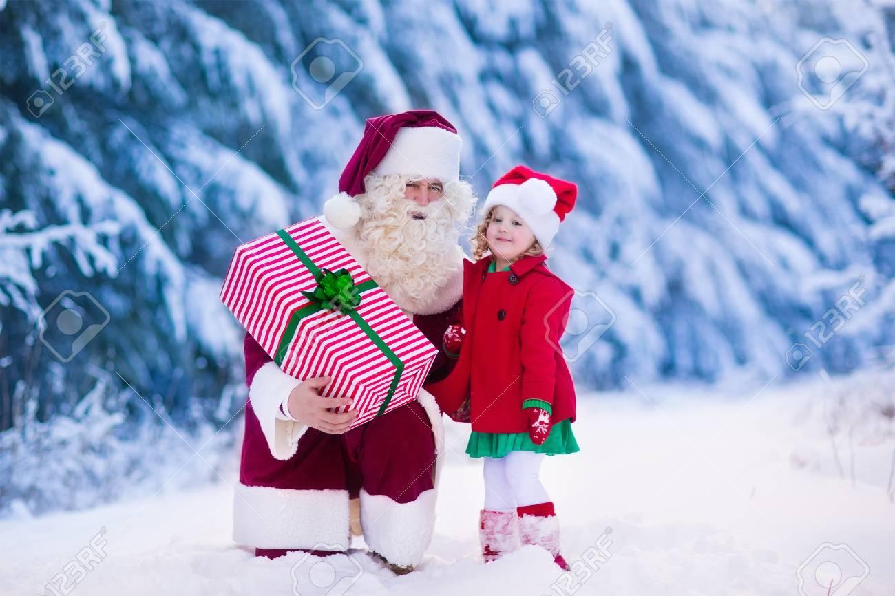 Weihnachtsmann Und Die Kinder öffnen Geschenke Im Schneebedeckten ...