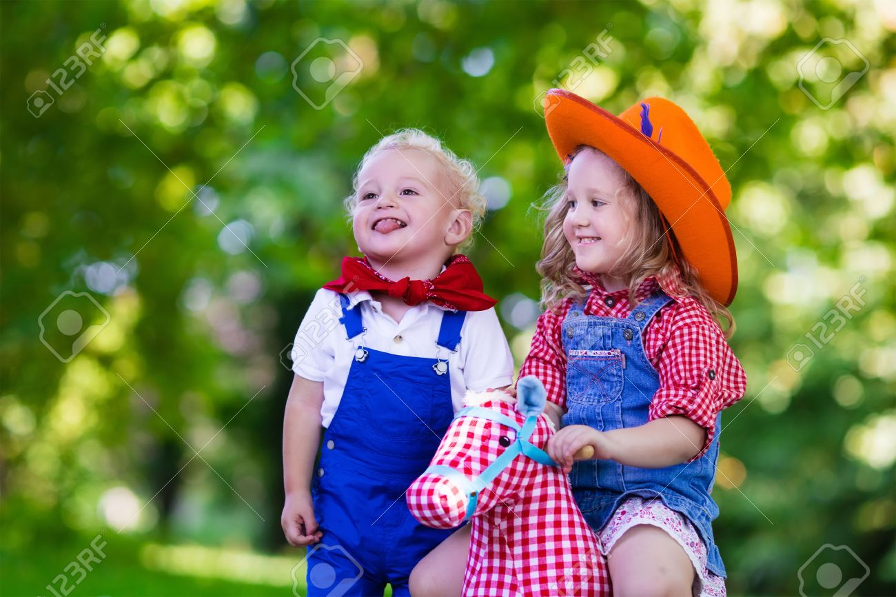 Niño Y Niña Vestidos Como Vaquero Y Vaquera Juega Con El Juguete Caballo De Oscilación En El Parque Los Niños Juegan Al Aire Libre Niños En
