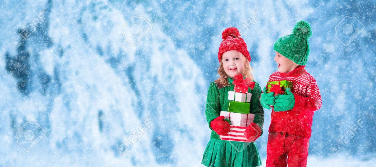 Kleine Mädchen Und Jungen In Roten Und Grünen Strickmütze Hält ...