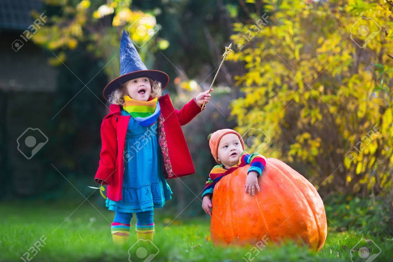 little girl in witch costume and baby boy in huge pumpkin playing in autumn park