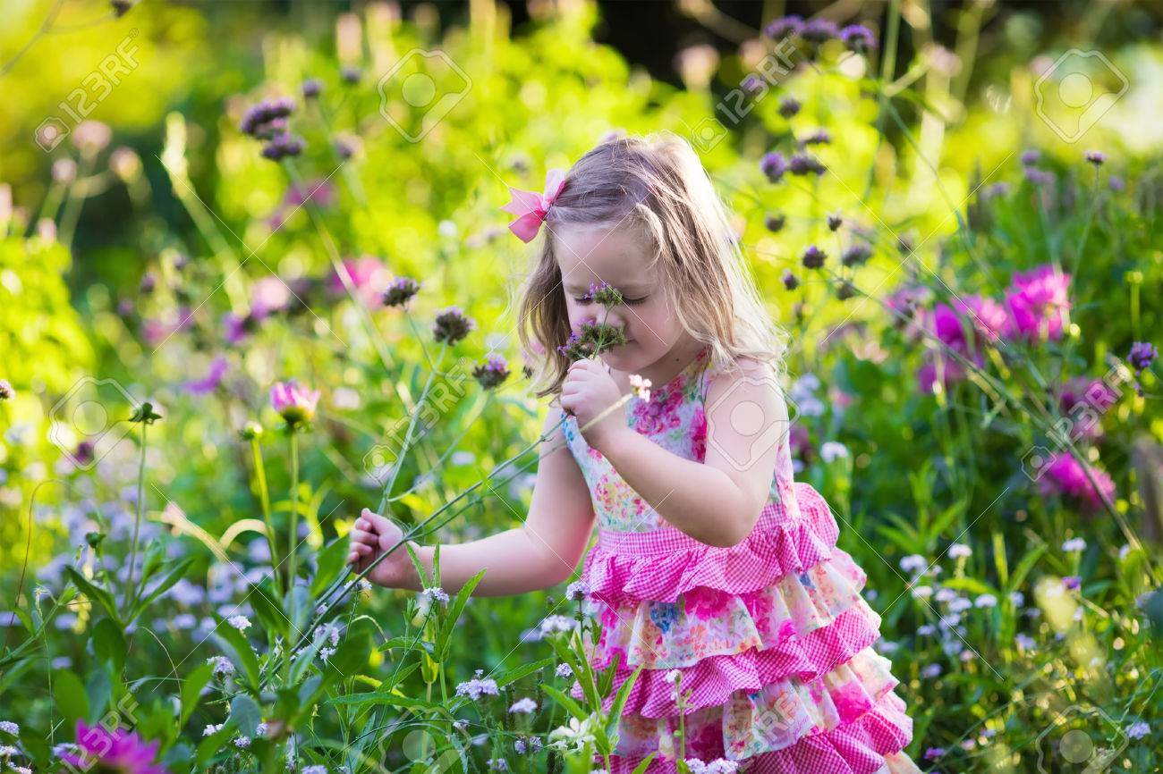 Little Girl Playing With Flowers In The Garden Kids Play Outdoors