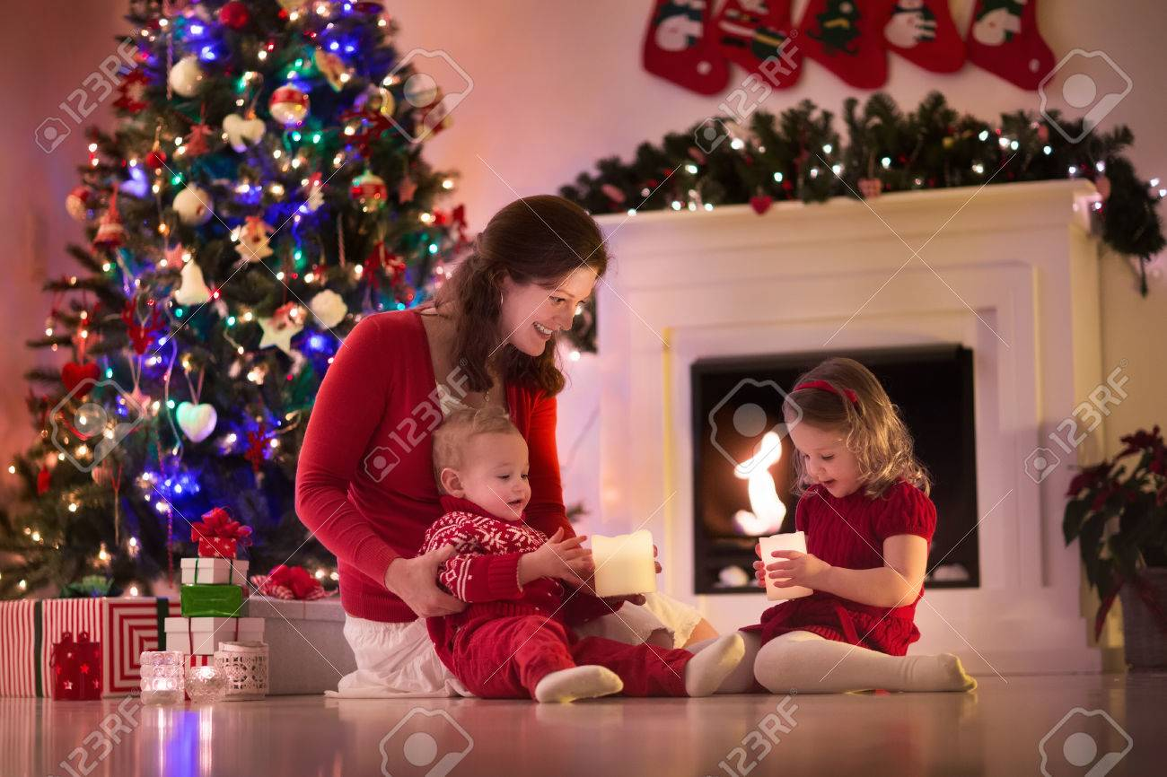 Family On Christmas Eve At Fireplace. Mother And Little Kids ...