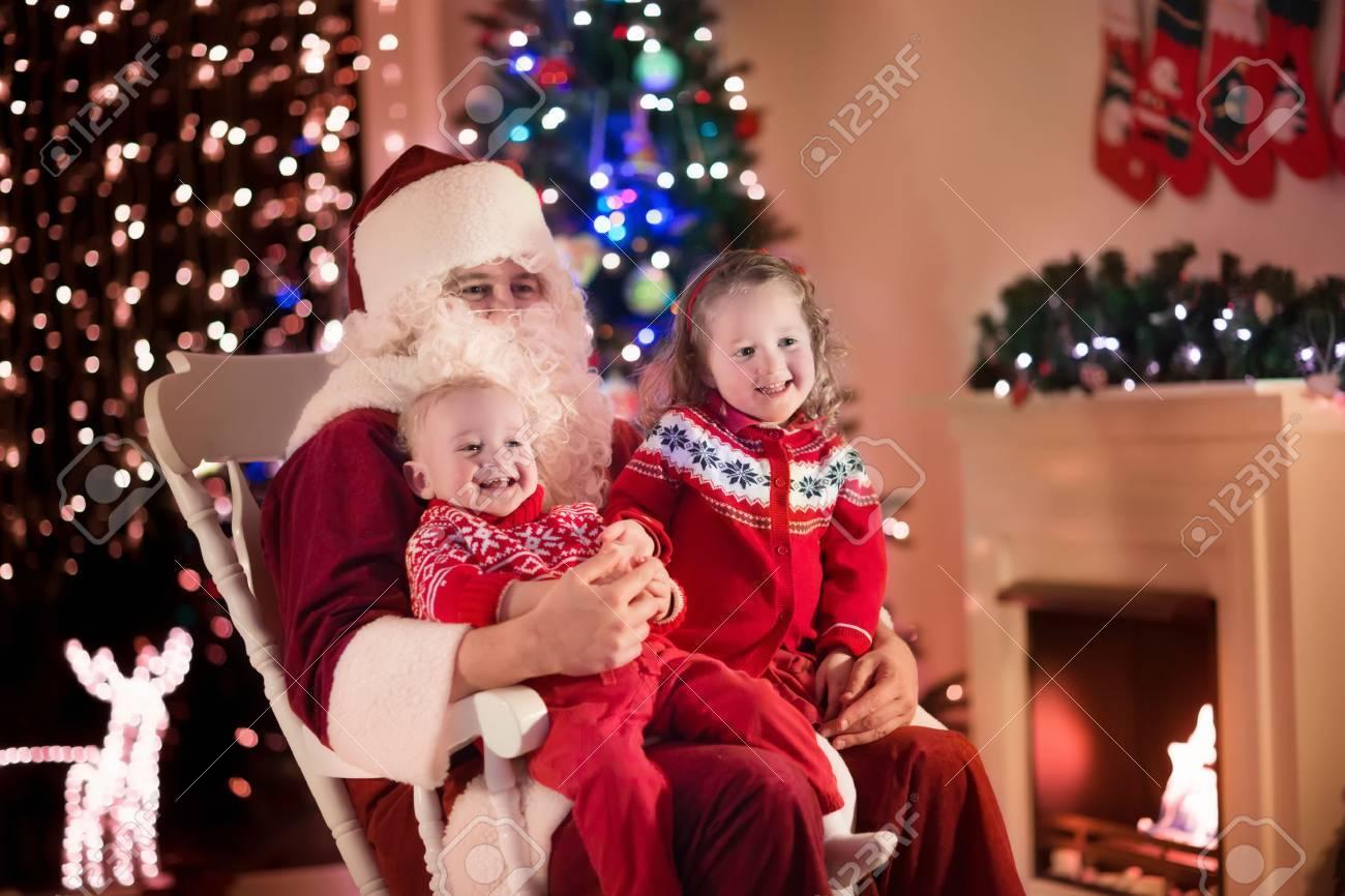 Weihnachtsmann Und Die Kinder öffnen Geschenke Am Kamin. Kinder Und ...