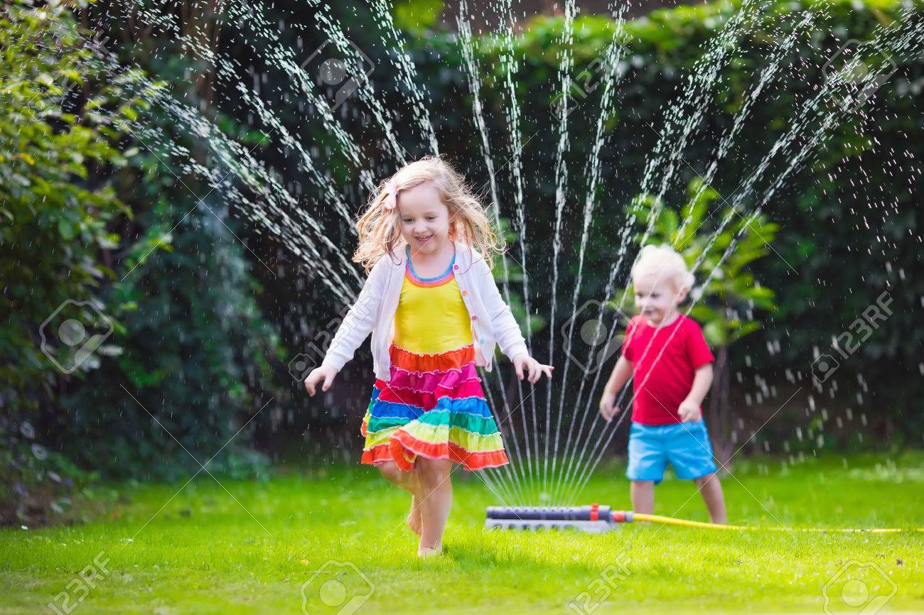 kids play water Child playing with garden sprinkler. Preschooler kid running and jumping.  Summer outdoor water fun