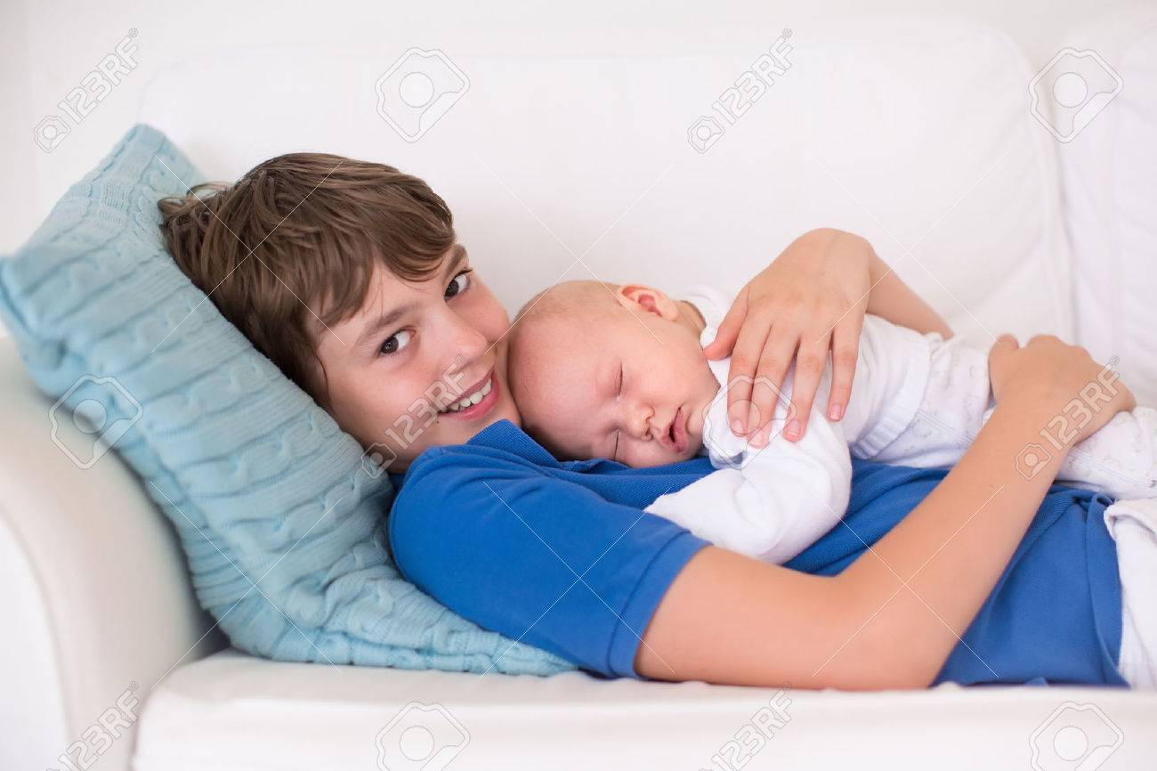 Happy laughing boy holding his sleeping newborn baby brother siblings with big age difference children playing at home on a white couch