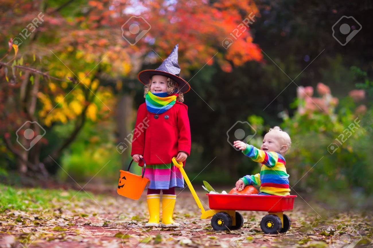 Little Girl In Witch Costume And Baby Boy In Wheel Barrow Holding ...