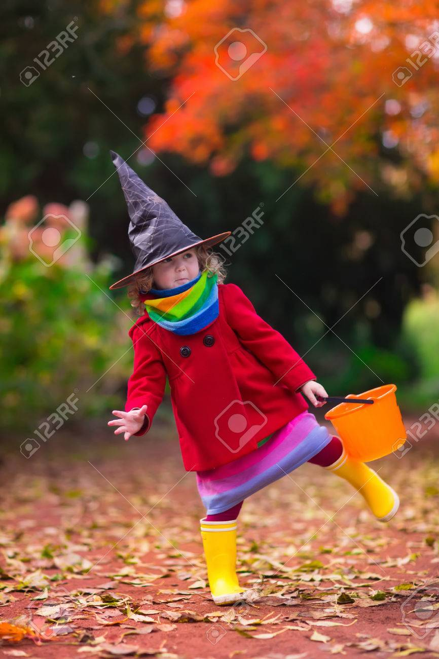 little girl in witch costume playing in autumn park child having fun at halloween trick