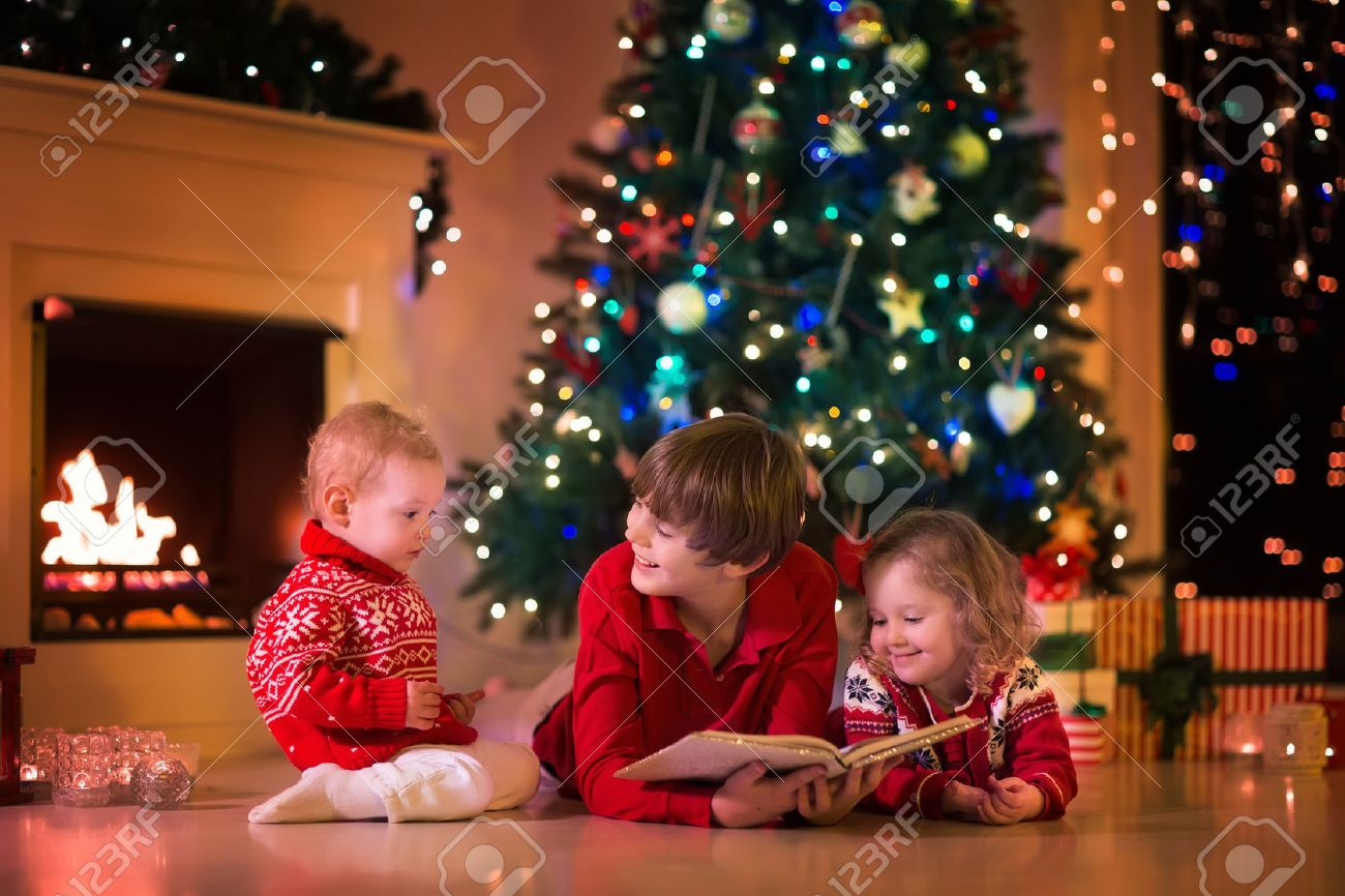 Children Read A Book And Open Gifts At Fireplace On Christmas ...
