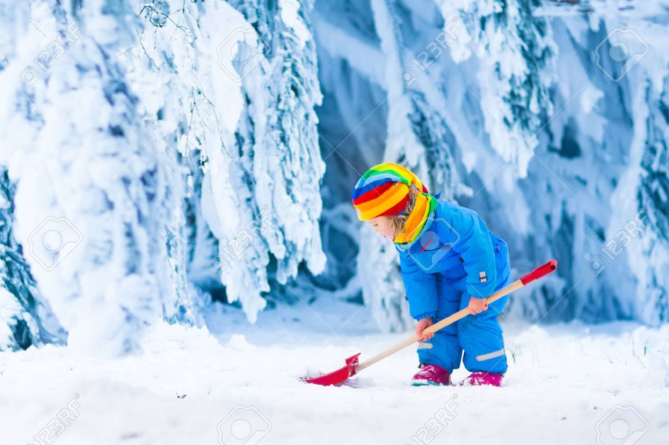 Little girl shoveling snow on home drive way. Beautiful snowy garden or front yard. Child with shovel playing outdoors in winter season. Family removing snow after blizzard. Kids play outside. - 46795776