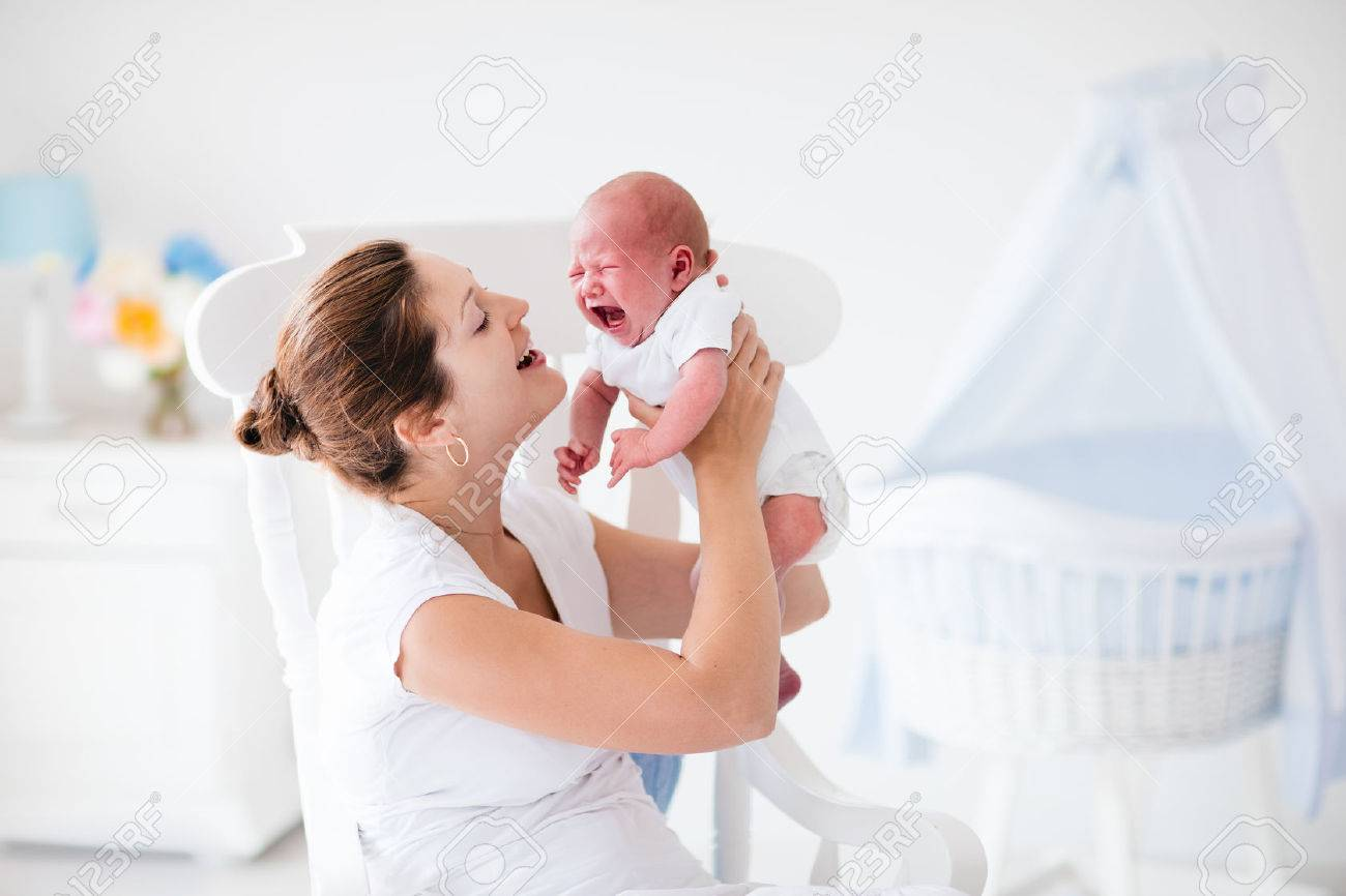 Young mother holding her newborn child mother comforting crying hungry baby woman and new born boy relax in a white bedroom with rocking chair and blue