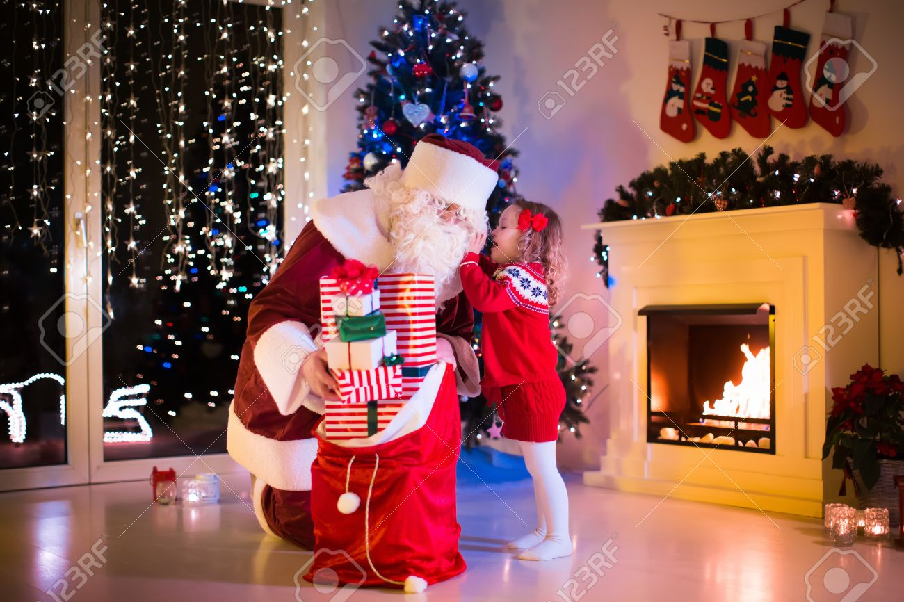 Children And Santa Claus At Fireplace On Christmas Eve Family