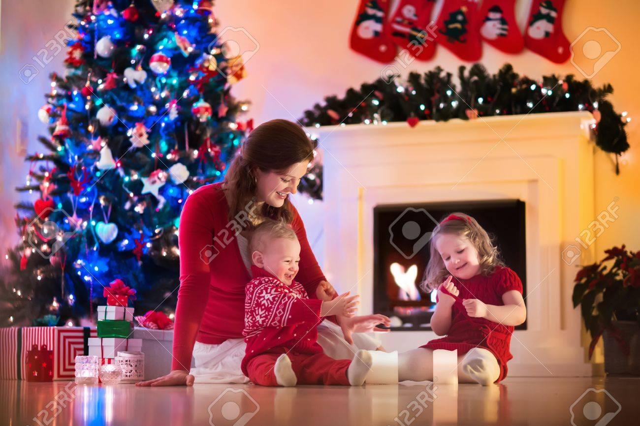Familie Am Weihnachtsabend Am Kamin. Mutter Und Kleine Kinder ...