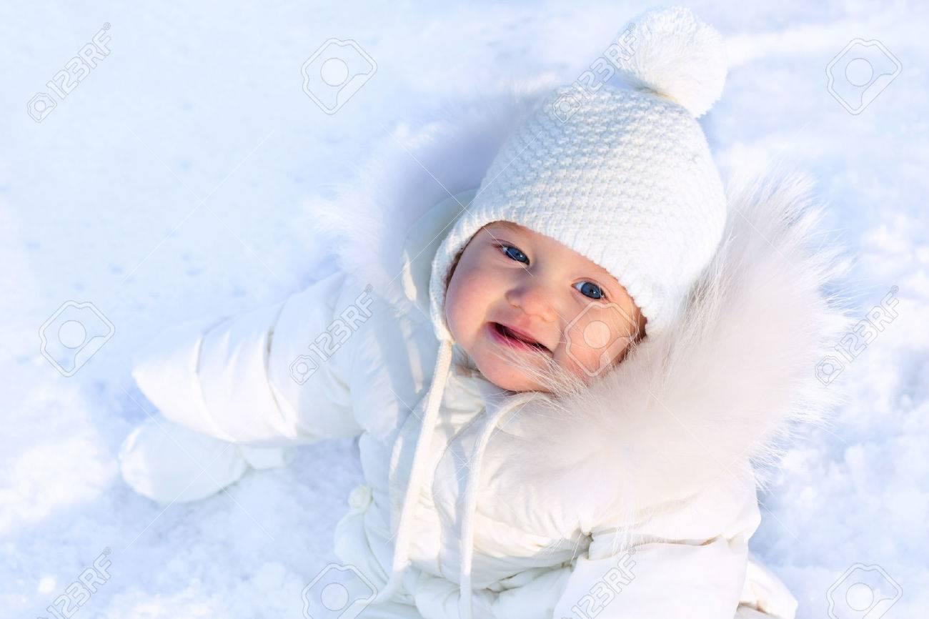 696367360df Drôle De Petite Fille De Bébé Dans Un Bonnet Tricoté Blanc Et Blanc Chaud  Manteau Jouer Avec La Neige. Les Enfants Jouent à L extérieur En Hiver.