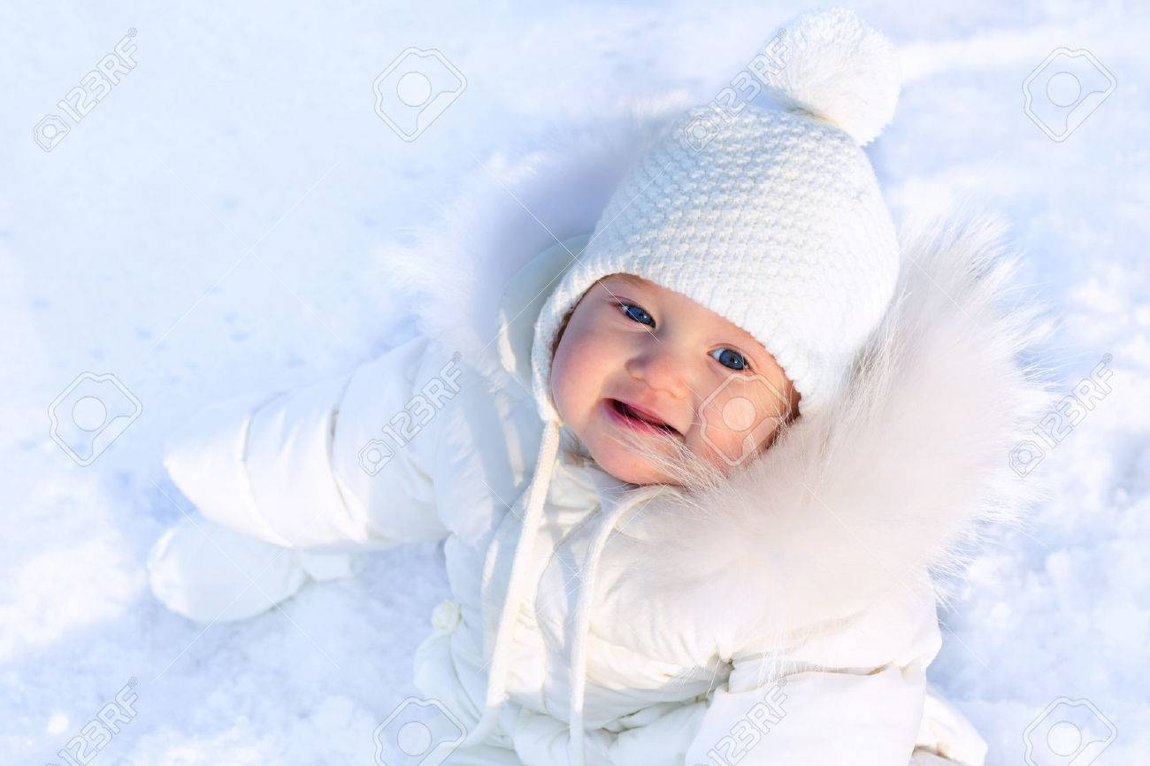 e6add17b78cf Funny Little Baby Girl In A White Knitted Hat And Warm White.. Stock ...