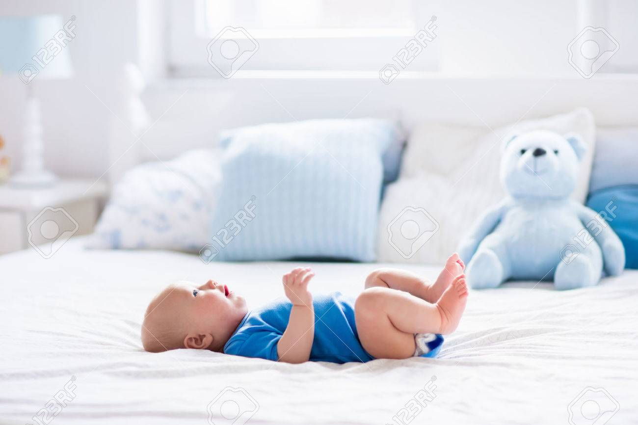 Entzückendes baby in der weißen sonnigen schlafzimmer. neugeborenes