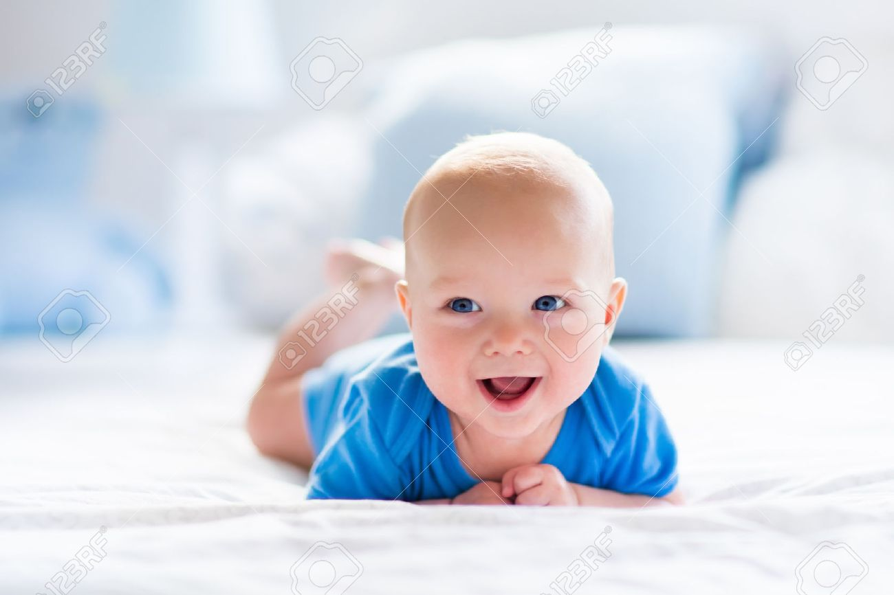 Adorable baby boy in white sunny bedroom. Newborn child relaxing in bed. Nursery for young children. Textile and bedding for kids. Family morning at home. New born kid during tummy time with toy bear. Stock Photo - 48829812