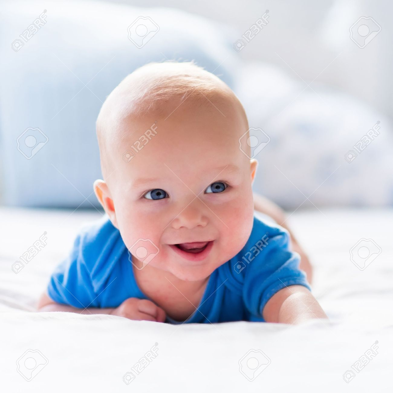 Adorable baby boy in white sunny bedroom. Newborn child relaxing in bed. Nursery for young children. Textile and bedding for kids. Family morning at home. New born kid during tummy time with toy bear. - 50840314
