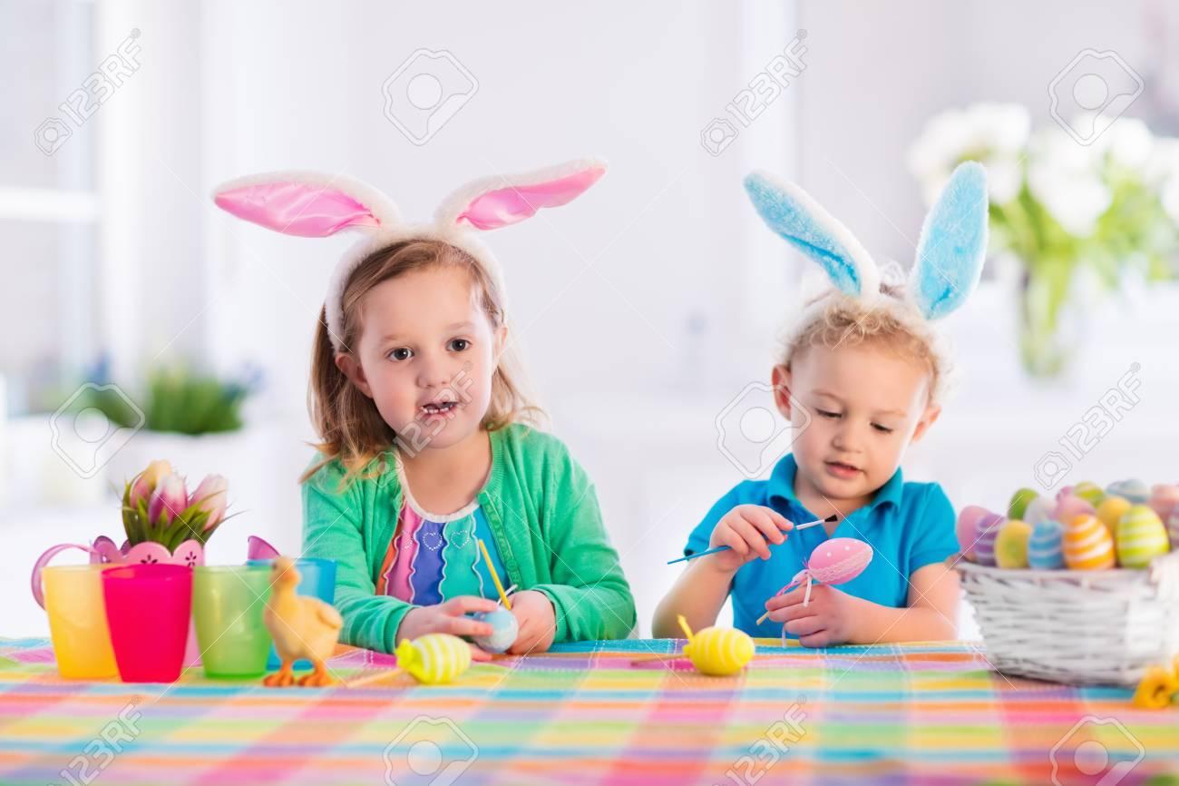 Niños Pintando Huevos De Colores. Los Niños Pintan Y Decoran Huevo ...