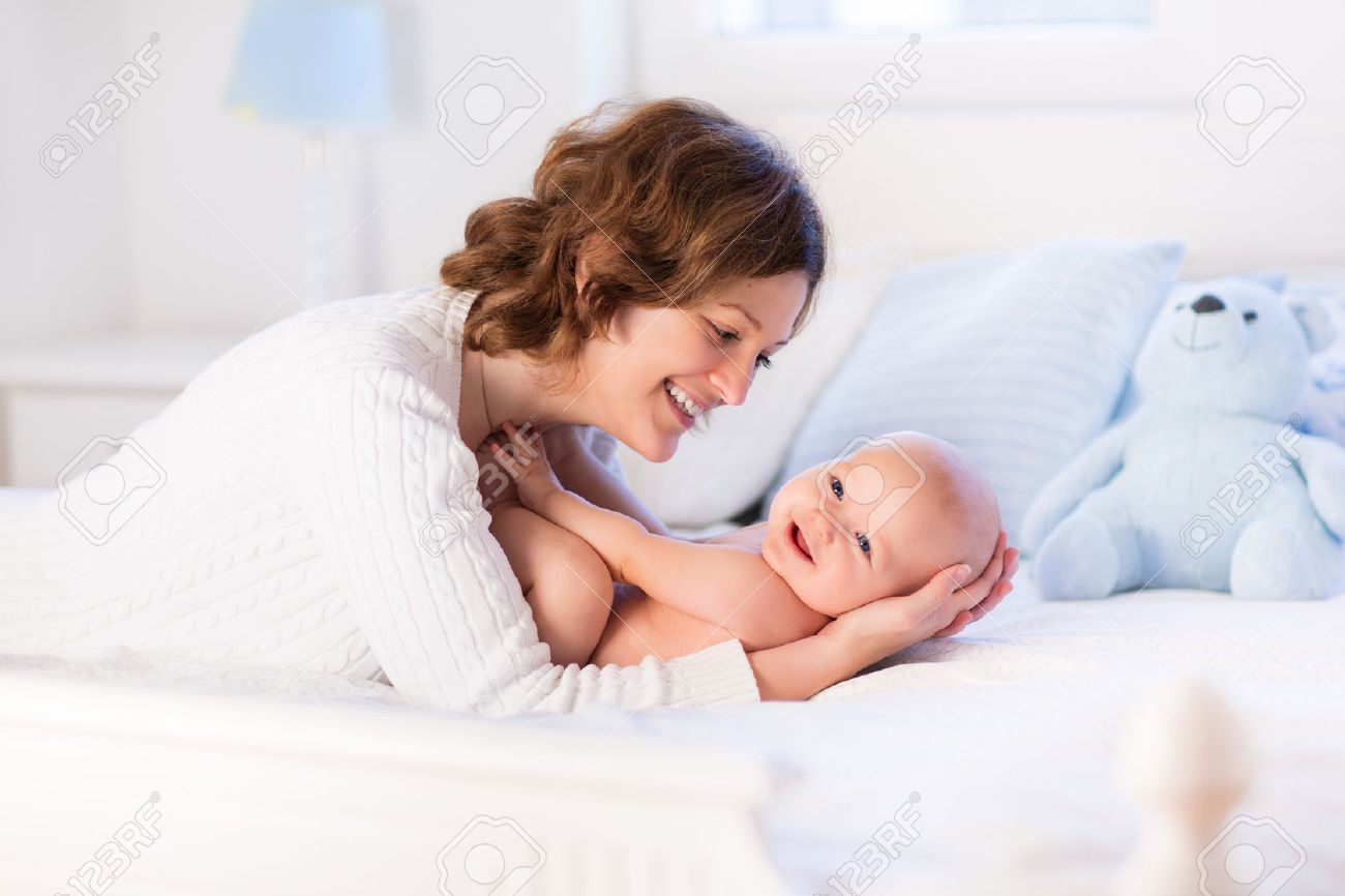 Mother and child on a white bed mom and baby boy in diaper playing in sunny bedroom parent and little kid relaxing at home family having fun together
